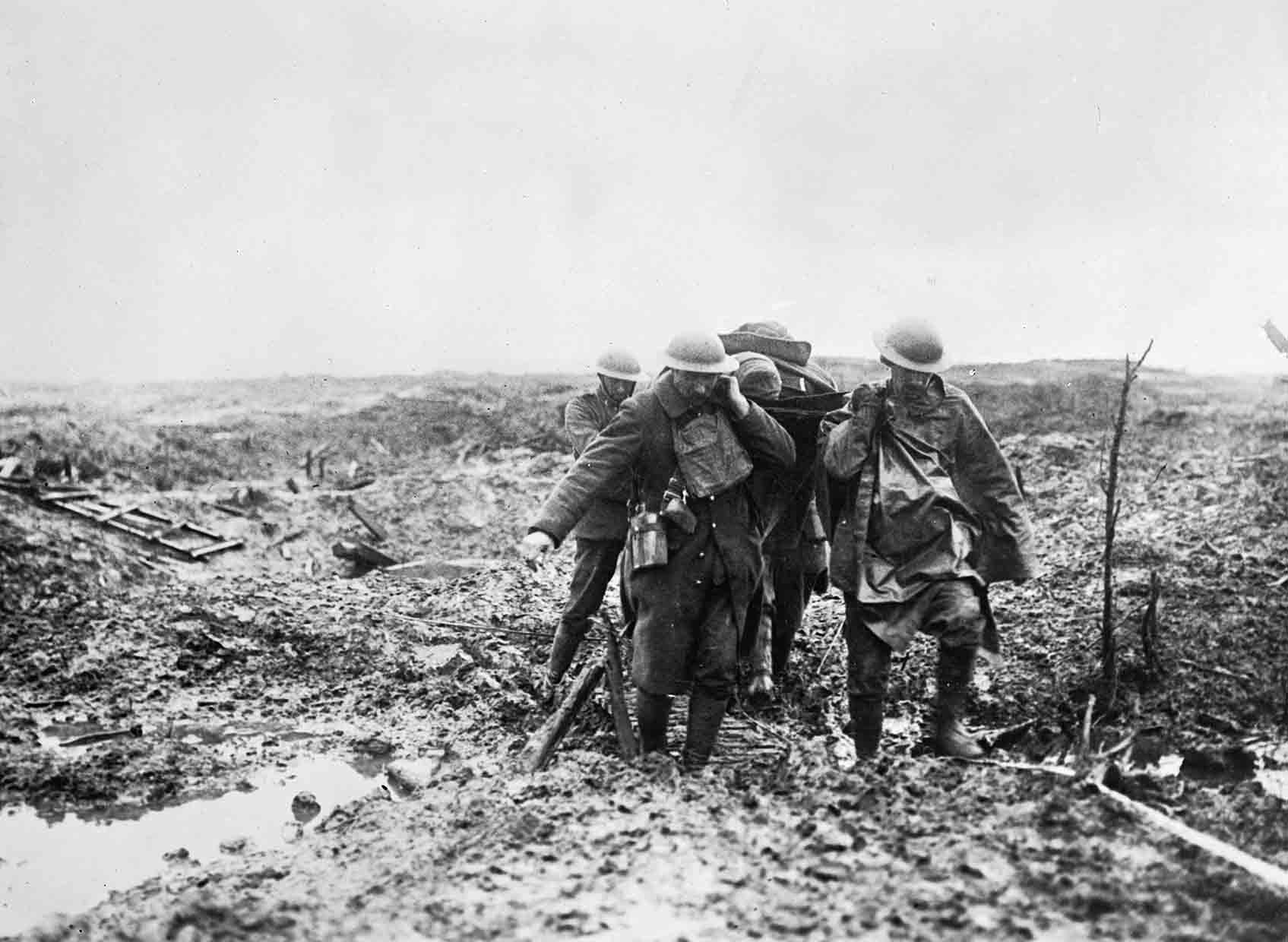 Stretcher bearers bringing in a wounded man over muddy ground at Passchendaele © IWM 2215 Otherwise please use - © IWM 2215
