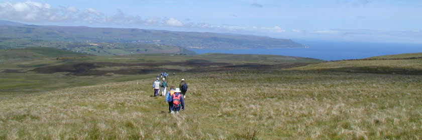 Photograph of people walking across the Glens of Antrim towards the coast