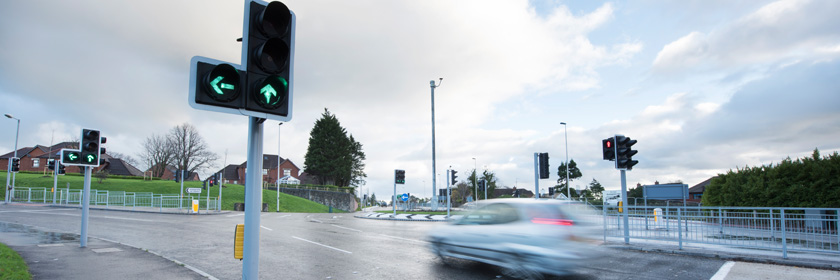 Photograph of a car driving past some traffic lights