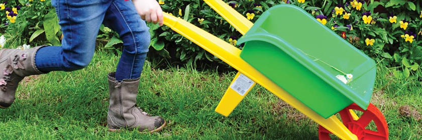 Photograph of a child pushing a wheelbarrow