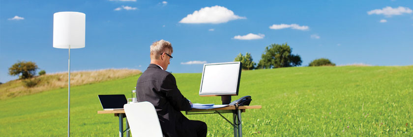 Photograph of a man sitting at a desk in an open field