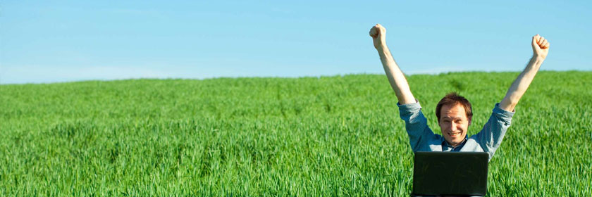 Photograph of a man sitting in a field cheering