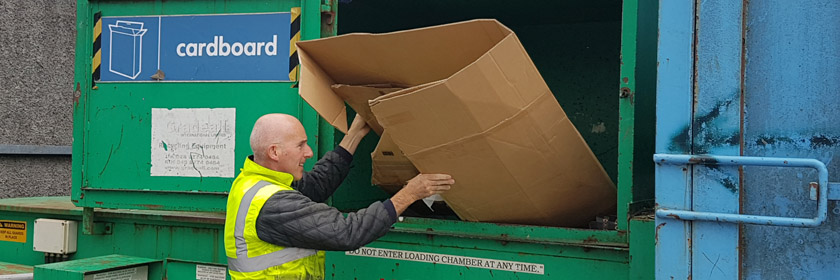 Photograph of someone recycling cardboard