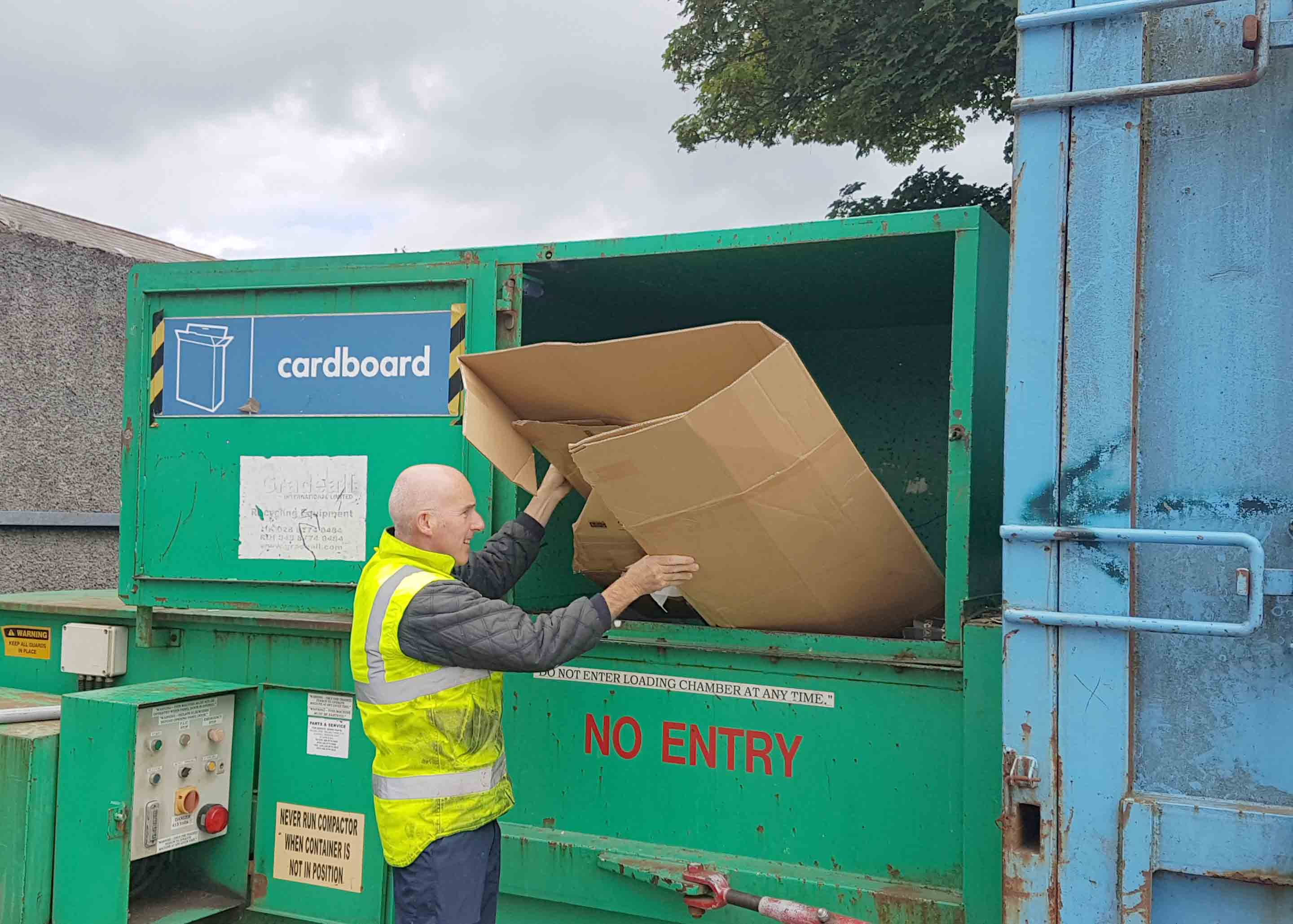 Photograph of a staff member recycling some cardboard