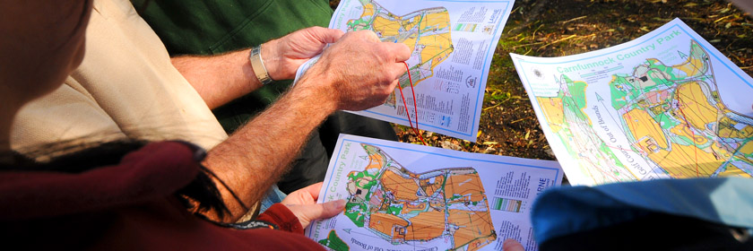 Photograph of people looking at orienteering maps