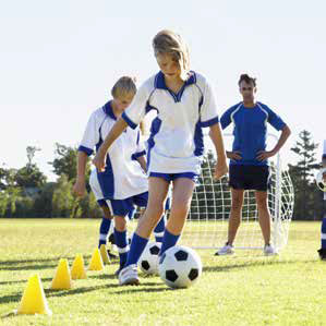 a group of young girls doing football skills exercises