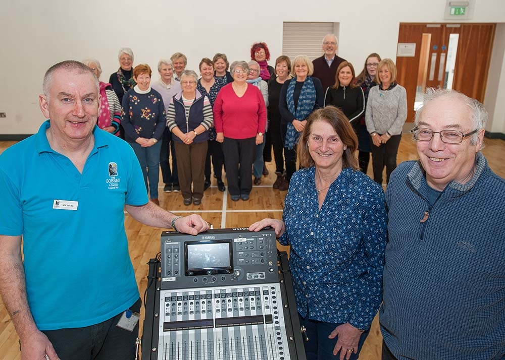 Michael from the Islandmagee Community Centre alongside Hilary and Eric Bailey, with the Island Voices Choir enjoying their new sound system