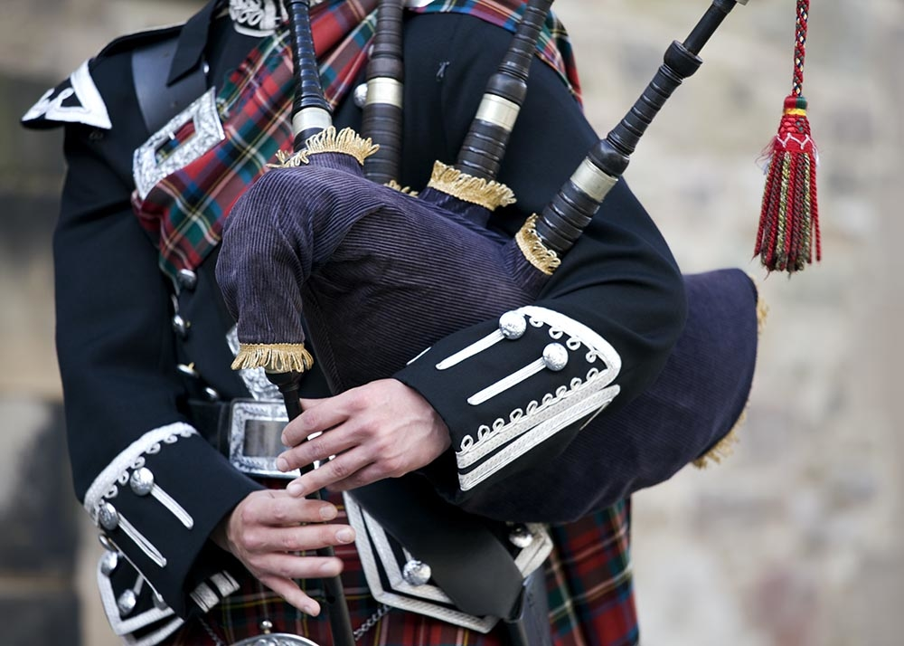 Close-up mid section of a man playing the Scottish bagpipes - Stock image